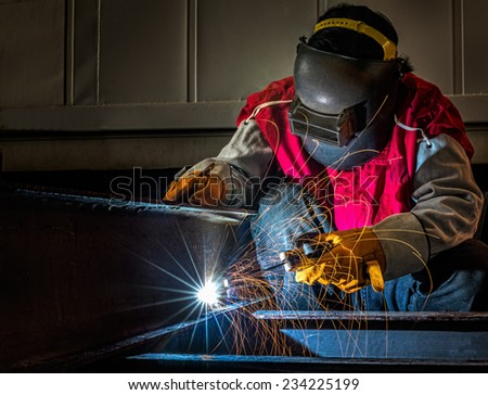 worker work hard with welding process in production plant - stock photo