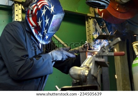 Worker work hard with welding process in production plant into a metal warehouse. Construction of mufflers for cars - stock photo