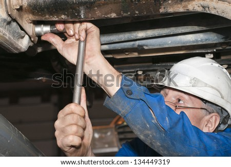 worker working on a broken down truck - stock photo