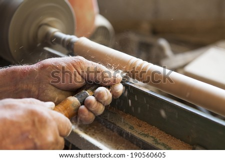 Worker working on wood with no safety equipment - stock photo