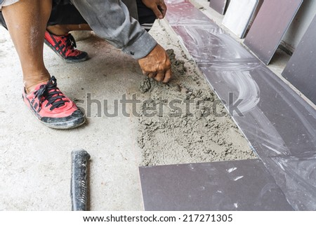 Worker working tiled in a construction site. - stock photo