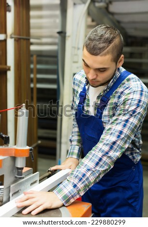 Worker working with PVC  on  machine at  plant - stock photo