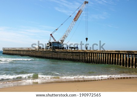 Workers and mobile crane on construction site of new pier on north beach in Durban South Africa - stock photo