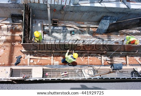 Workers are fixing the tie rods with plastic cones onto the wooden formworks. The function of it is to resist the horizontal pressure caused by the freshly placed concrete later. - stock photo