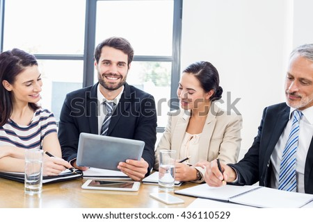 Workers are looking at a notebook and one of them is looking in front of him and smiling at work