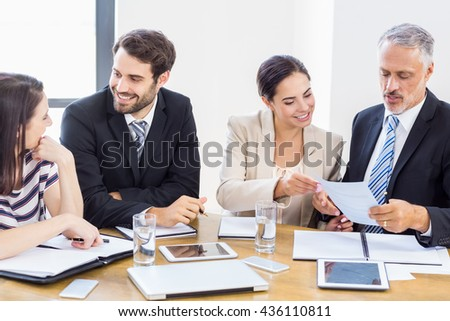 Workers are talking to each other and smiling at work