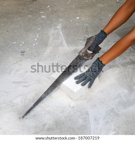 Workers are using a saw to cut Concrete to a smaller demand in building construction.