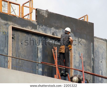Workers at a construction site. Concrete background - stock photo