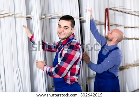 Workers at a window production factory selecting a specific PVC profile panel - stock photo