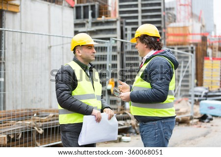 Workers at construction site reviewing plans