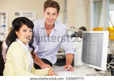Workers At Desk In Busy Creative Office - stock photo