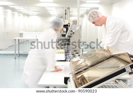 Workers at modern drug factory - stock photo