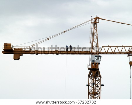 Workers atop a multistory construction crane.  Each is engaged in a different form of communication ... one on a cell phone, the other s hauling something up by rope - stock photo