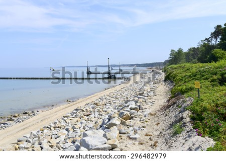 Workers build a breakwater to facilitate the construction of the beach in Ustka, Poland. - stock photo