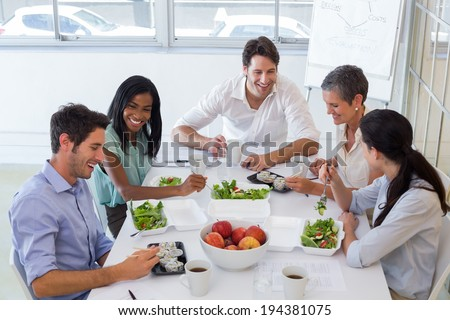 Workers chatting while enjoying healthy lunch in the office - stock photo