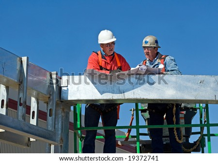 Workers Checking the Blueprints - stock photo
