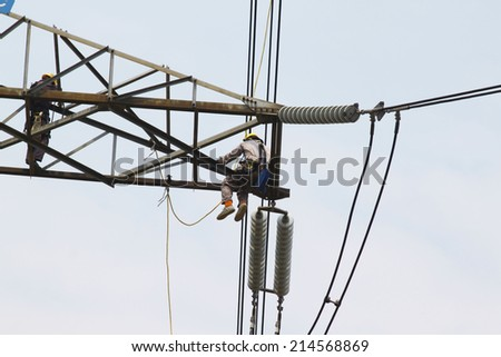Workers clean the insulation on high voltage transmission line - stock photo