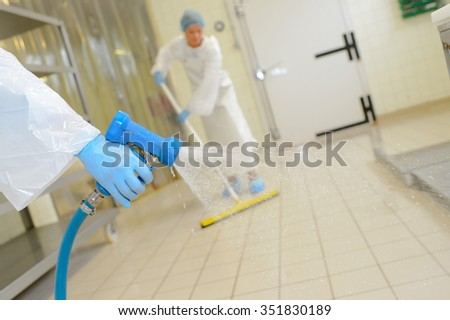Workers cleaning down factory floor