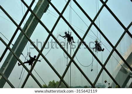 workers cleaning windows service on high  building