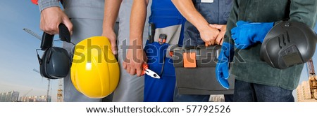 workers closeup with equipment on building background - stock photo