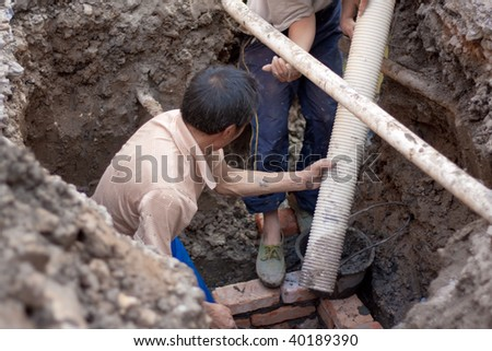 Workers collaborating to install new sewer pipes - stock photo