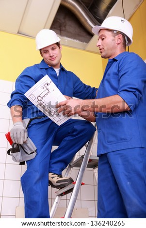 Workers discussing a drawing - stock photo