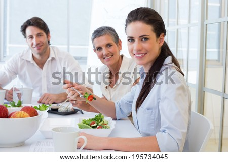 Workers eating lunch smile at camera in the office - stock photo