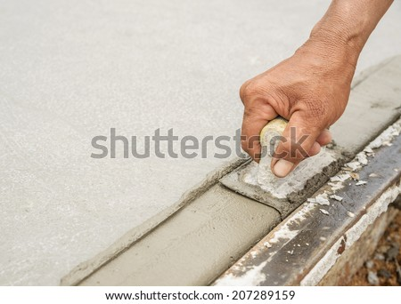 Workers hand using trowel with wet concrete, Construction road with cement. Selective focus.  - stock photo