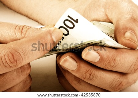 Workers hands counting hundred euro banknotes, sepia toned image - stock photo