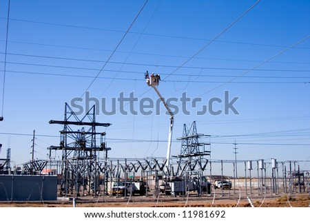 Workers in a bucket working on high tension power wires. - stock photo