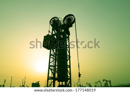 Workers in a tower of pumping unit under the setting sun   - stock photo