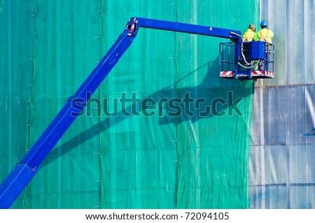 Workers in crane's basket - stock photo