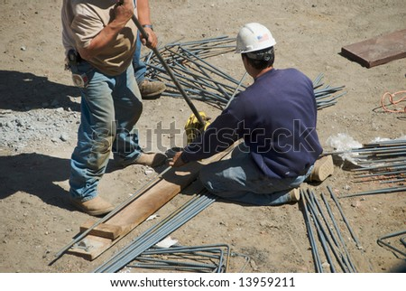 Workers in dusty building site use rebar bender to prepare rods for concrete pouring - stock photo