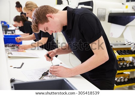 Workers In Engineering Factory Checking Component Quality