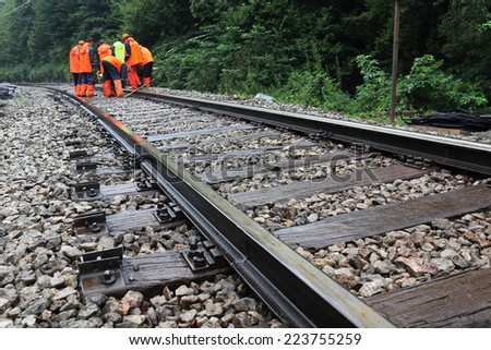 Workers in orange  raincoats repair railroad on rainy day - stock photo