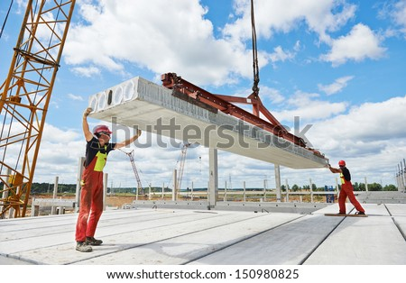 workers in safety protective equipment installing concrete floor slab panel at building construction site - stock photo