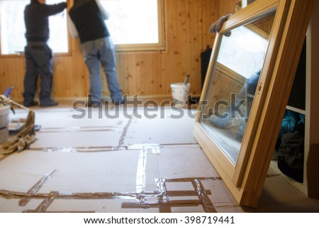 Workers in the background installing new, three pane wooden windows in an old wooden house, with a new window in the foreground. Home renovation, sustainable living, energy efficiency concept.  - stock photo