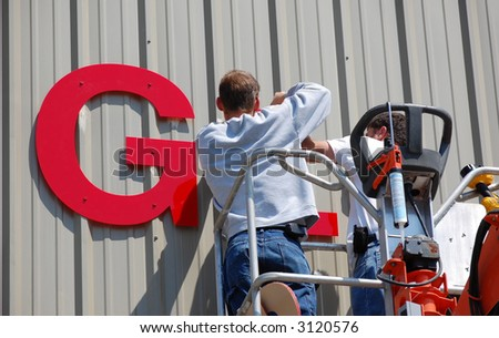 Workers install a sign on the side of an industrial building. - stock photo