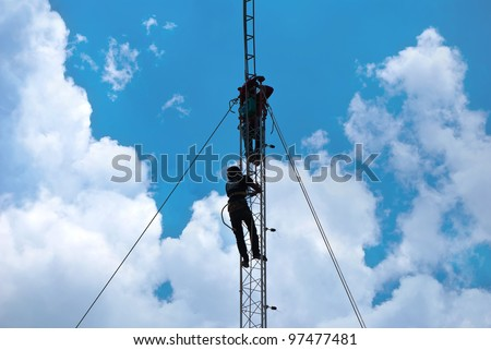 Workers install cellular antenna - stock photo