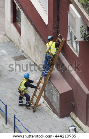 WORKERS INSTALLING CABLE WITH A STAIR OR WIRING