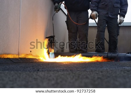 Workers installing roofing felt with heat - stock photo