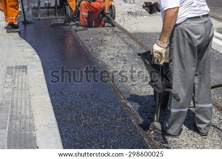 Workers laying stone mastic asphalt during street repairing works. Selective focus and shallow dof. - stock photo