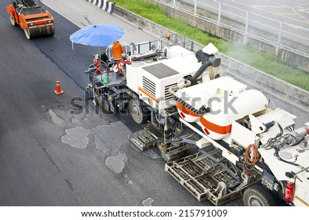 Workers making asphalt with shovels at road construction and Road rollers during asphalt paving works for repairing blacktopping transportation street. - stock photo