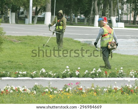 workers mow the lawn - stock photo