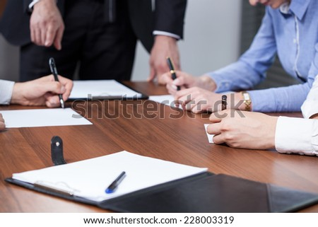 Workers of a corporation sitting at a table and writing