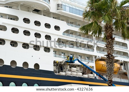 workers on a lift inspecting and making repairs to a cruise ship in port