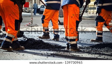 Workers on a road construction, industry and teamwork. People working on an asphalt road with shovels. - stock photo