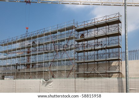 Workers on scaffolding on a construction site, Europe, Italy