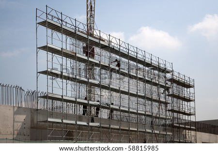 Workers on scaffolding on a construction site, Europe, Italy - stock photo