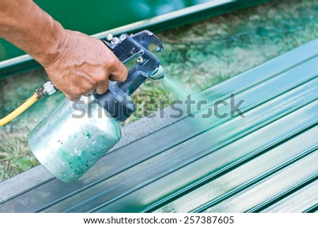 workers painted green for sheet metal  - stock photo